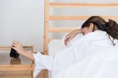 Νέα γυναίκα που παίρνει τονισμένη για να ξυπνήσει στοκ φωτογραφίες