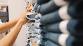Νέα γυναίκα που παίρνει το ζευγάρι των μπλε τζιν τζιν από τους σωρούς στο κατάστημα ιματισμού Θηλυκά χέρια που επιλέγουν το σωστό απόθεμα βίντεο