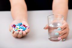 Νέα γυναίκα που παίρνει το χάπι ή το φάρμακο με το ποτήρι του νερού, στοκ φωτογραφία με δικαίωμα ελεύθερης χρήσης