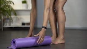 Νέα γυναίκα που παίρνει το χαλί γιόγκας από το πάτωμα, που παίρνει έτοιμο για τη γυμναστική, δραστηριότητα απόθεμα βίντεο