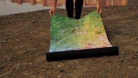 Νέα γυναίκα που παίρνει το χαλί γιόγκας από το πάτωμα απόθεμα βίντεο