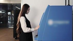 Νέα γυναίκα που παρεμβάλλει μια πιστωτική κάρτα στο ATM, όμορφο κορίτσι που καταθέτει το ανέπαφο nfc στο τερματικό αερολιμένων λε απόθεμα βίντεο