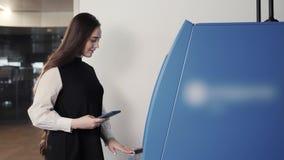 Νέα γυναίκα που παρεμβάλλει μια πιστωτική κάρτα στο ATM, όμορφο κορίτσι που καταθέτει το ανέπαφο nfc στο τερματικό αερολιμένων λε φιλμ μικρού μήκους