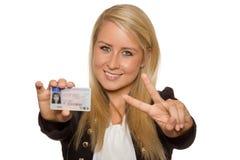 Νέα γυναίκα που παρουσιάζει άδεια του οδηγού της στοκ φωτογραφία με δικαίωμα ελεύθερης χρήσης