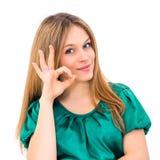 Νέα γυναίκα που παρουσιάζει ΕΝΤΑΞΕΙ χαμόγελο σημαδιών χεριών ευτυχές Στοκ εικόνα με δικαίωμα ελεύθερης χρήσης