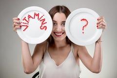 Νέα γυναίκα που παρουσιάζει πιάτα στοκ φωτογραφία