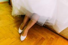 Νέα γυναίκα που παρουσιάζει πόδια της με τα μοντέρνα άσπρα παπούτσια Στοκ εικόνα με δικαίωμα ελεύθερης χρήσης
