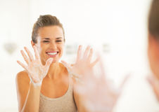 Νέα γυναίκα που παρουσιάζει σαπωνώδη χέρια Στοκ φωτογραφία με δικαίωμα ελεύθερης χρήσης
