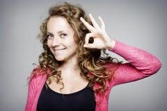 Νέα γυναίκα που παρουσιάζει στο χέρι εντάξει σημάδι Στοκ Εικόνες