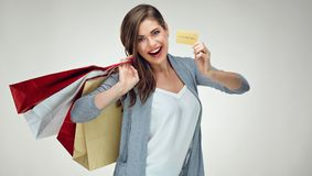 Νέα γυναίκα που παρουσιάζει τη χρυσή πιστωτική κάρτα και που κρατά την τσάντα αγορών στοκ εικόνες