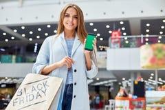 Νέα γυναίκα που παρουσιάζει τις αγορές App Στοκ Εικόνα