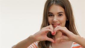 Νέα γυναίκα που παρουσιάζει χειρονομία μορφής καρδιών απόθεμα βίντεο
