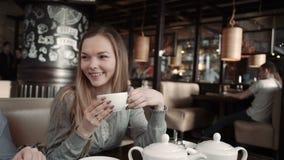 Νέα γυναίκα που περιμένει κάποιο σε έναν καφέ Πίνει το τσάι και μιλά με τους φίλους Χαμόγελο και εξέταση φιλμ μικρού μήκους