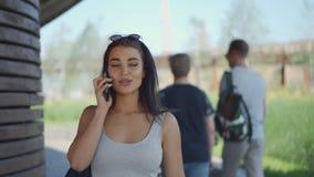 Νέα γυναίκα που περπατά και που καλεί τηλεφωνικώς απόθεμα βίντεο