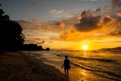 Νέα γυναίκα που περπατά και που χαλαρώνει σε μια τροπική παραλία στους ήλιους Στοκ Φωτογραφίες
