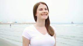 Νέα γυναίκα που περπατά κατά μήκος της παραλίας μόνο Αέρας από τη Μεσόγειο που φυσά την τρίχα της σε σε αργή κίνηση φιλμ μικρού μήκους