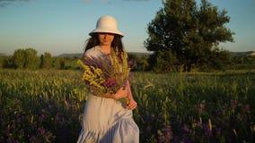 Νέα γυναίκα που περπατά με την ανθοδέσμη των λουλουδιών τομέων απόθεμα βίντεο