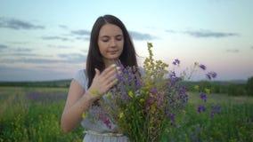Νέα γυναίκα που περπατά με την ανθοδέσμη των λουλουδιών τομέων φιλμ μικρού μήκους