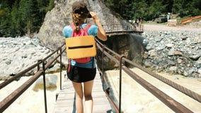 Νέα γυναίκα που περπατά πέρα από την ξύλινη γέφυρα πέρα από τον ποταμό βουνών απόθεμα βίντεο