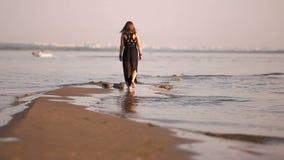 Νέα γυναίκα που περπατά στα πόδια ακτών γραμμών ίσαλων γραμμών απόθεμα βίντεο