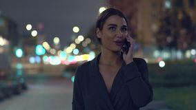 Νέα γυναίκα που περπατά στην πόλη νύχτας και που μιλά με τους φίλους απόθεμα βίντεο