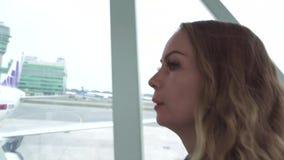 Νέα γυναίκα που περπατά στην τροφή του διαδρόμου στο αεροπλάνο στο τερματικό αερολιμένων Κλείστε επάνω ανησυχημένο το πορτρέτο κο απόθεμα βίντεο