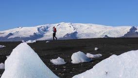 Νέα γυναίκα που περπατά στη μαύρη παραλία παγόβουνων άμμου απόθεμα βίντεο