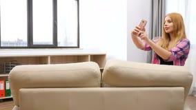 Νέα γυναίκα που περπατά στον καναπέ και που παίρνει ένα selfie σε τον απόθεμα βίντεο