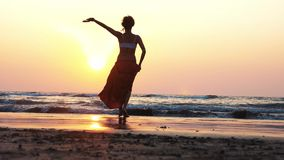 Νέα γυναίκα που περπατά χωρίς παπούτσια προς τη θάλασσα στο όμορφο ηλιοβασίλεμα, οπισθοσκόπο απόθεμα βίντεο