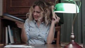 Νέα γυναίκα που πηγαίνει τρελλή στον εργασιακό χώρο της και που χορεύει με τα βιβλία μετά από να τελειώσει ένα μακροχρόνιο πρόγρα Στοκ φωτογραφίες με δικαίωμα ελεύθερης χρήσης