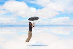 Νέα γυναίκα που πηδά με την ομπρέλα Στοκ φωτογραφία με δικαίωμα ελεύθερης χρήσης
