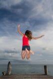 Νέα γυναίκα που πηδά στην αποβάθρα Στοκ εικόνα με δικαίωμα ελεύθερης χρήσης
