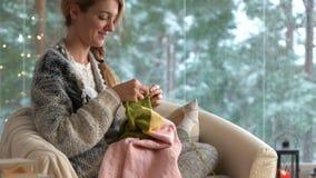Νέα γυναίκα που πλέκει το θερμό πουλόβερ μαλλιού στο δωμάτιο συνεδρίασης ενάντια στο τοπίο χιονιού από το εξωτερικό φιλμ μικρού μήκους