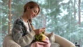 Νέα γυναίκα που πλέκει το θερμό πουλόβερ μαλλιού στο δωμάτιο συνεδρίασης ενάντια στο τοπίο χιονιού από το εξωτερικό απόθεμα βίντεο