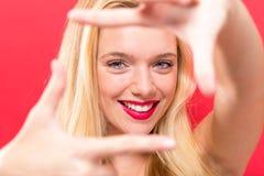 Νέα γυναίκα που πλαισιώνει το πρόσωπό της με τα δάχτυλά της Στοκ Φωτογραφίες
