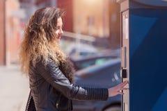 Νέα γυναίκα που πληρώνει για το χώρο στάθμευσης στοκ εικόνες