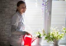 Νέα γυναίκα που ποτίζει τα εσωτερικά λουλούδια στοκ εικόνες