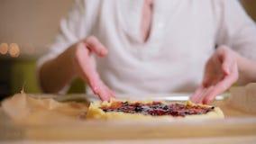 Νέα γυναίκα που προετοιμάζει ένα εορταστικό κέικ στην κουζίνα Στο όμορφο bokeh υποβάθρου φιλμ μικρού μήκους