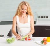 Νέα γυναίκα που προετοιμάζει τη φυτική σαλάτα στοκ εικόνες