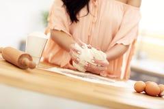 Νέα γυναίκα που προσπαθεί να μαγειρεψει κάτι στην κουζίνα Στοκ εικόνα με δικαίωμα ελεύθερης χρήσης