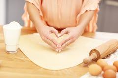 Νέα γυναίκα που προσπαθεί να μαγειρεψει κάτι στην κουζίνα Στοκ Εικόνες