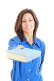 Νέα γυναίκα που προσφέρει ή που δίνει το βιβλίο Στοκ Εικόνες