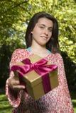 Νέα γυναίκα που προσφέρει το κιβώτιο δώρων Στοκ Φωτογραφίες