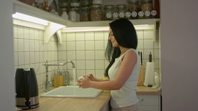 Νέα γυναίκα που πλένει τα βρώμικα πιάτα με το σαπούνι και που μιλά σε κάποιο στην εγχώρια κουζίνα φιλμ μικρού μήκους
