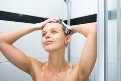 Νέα γυναίκα που πλένει την τρίχα της με το σαμπουάν Στοκ Εικόνα
