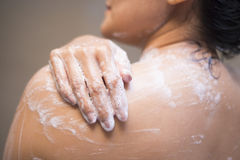 Νέα γυναίκα που πλένει το σώμα της με το πήκτωμα ντους Στοκ Φωτογραφίες