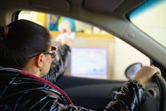 Νέα γυναίκα που πληρώνει το φόρο στην εθνική οδό στο tollbooth Στοκ Εικόνες