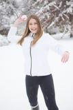 Νέα γυναίκα που ρίχνει τη σφαίρα χιονιού Στοκ Φωτογραφίες