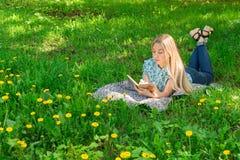 Νέα γυναίκα που σκέφτεται και που γράφει στο ημερολόγιό της στη χλόη με τα λουλούδια Μπροστινή όψη Στοκ εικόνα με δικαίωμα ελεύθερης χρήσης