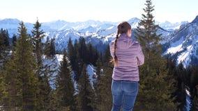Νέα γυναίκα που σκέφτεται και που εξετάζει τα βουνά φιλμ μικρού μήκους